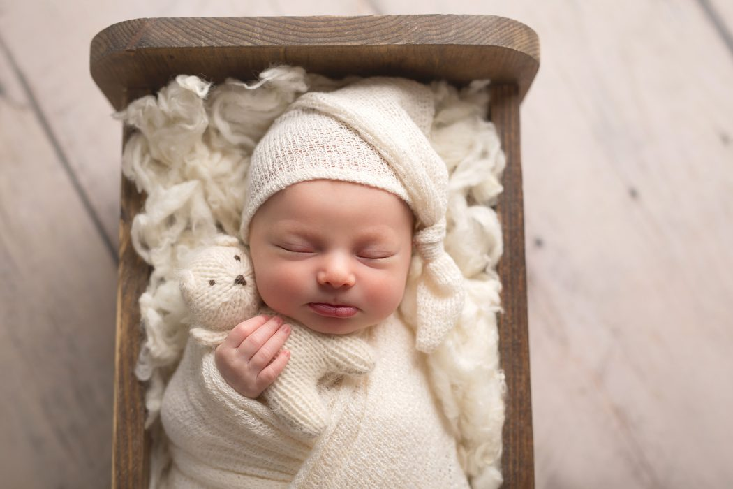 newborn baby sleeping in wooden bed holding white teddy bear